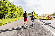 Young couple running on country road - UUF008085