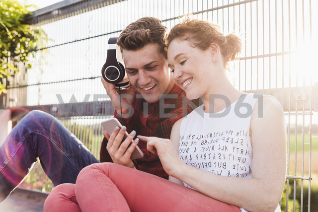 Smiling young couple at a fence with headphones and smartphone - UUF008112