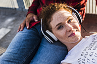 Young woman with headphones lying on boyfriend's lap - UUF008115