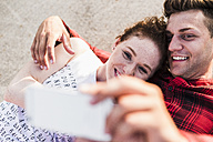 Smiling young couple lying down taking a selfie - UUF008118