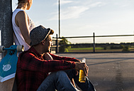 Young couple with skateboard and beer bottle enjoying the sunset - UUF008124