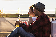 Young couple with beer bottles enjoying the sunset - UUF008127