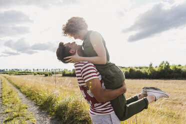 Happy young man lifting up girlfriend on field path - UUF008154
