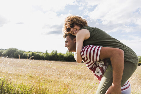Happy young man carrying girlfriend piggyback in the nature - UUF008157