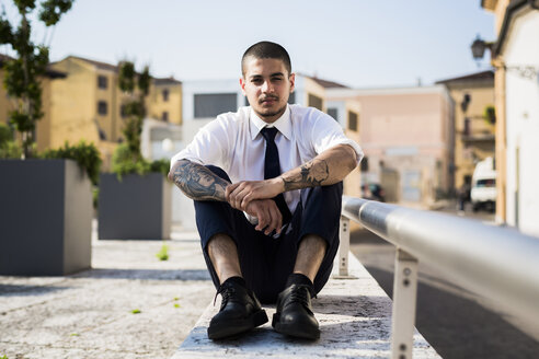 Portrait of young businessman with tatoos on his forearms sitting on a wall - GIOF001257