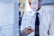Young businessman behind glass pane looking at cell phone - GIOF001263