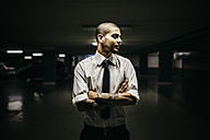 Young businessman with tattoos on his forearms standing in a gloomy car park - GIOF001266