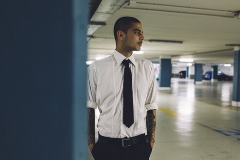 Young businessman standing in a  car park - GIOF001269