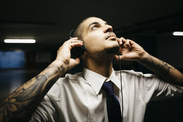 Young businessman with tattoo on his forearms with headphones in a gloomy car park - GIOF001272