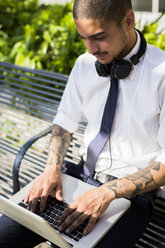 Young businessman sitting on a bench using laptop - GIOF001278