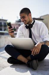 Smiling young businessman sitting on a wall with laptop looking at his cell phone - GIOF001281
