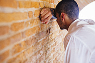 Young businessman leaning against brick wall - GIOF001287