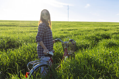 Young woman with bicycle standing in wheat field - DERF000031