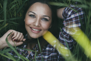 Portrait of smiling young woman  lying in a field - DERF000034