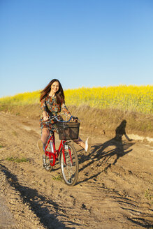 Young woman balancing on bicycle on a dirt track - DERF000040