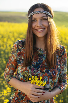Portrait of smiling young hippie standing in a rape field holding flowers - DERF000043