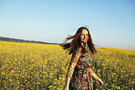 Portrait of smiling young woman standing in a rape field - DERF000046