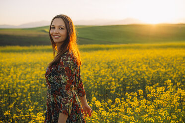 Smiling young woman standing in a rape field at twilight - DERF000049