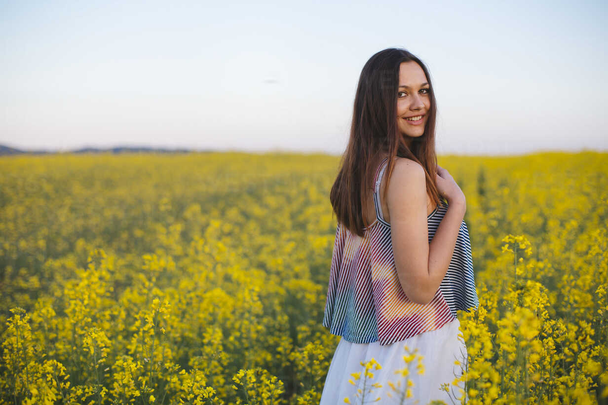 Smiling young woman standing in a rape field - DERF000052 - MelkinImages/Westend61