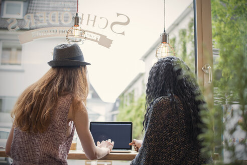 Two young women using laptop in a cafe - ONF000939