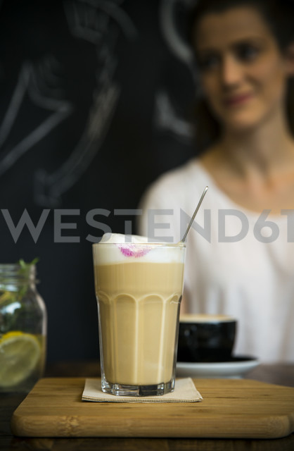 Glass of milk coffee on table in cafe with young woman in background - ONF000999 - noonland/Westend61