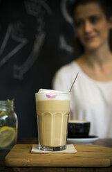 Glass of milk coffee on table in cafe with young woman in background - ONF000999