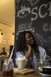 Young woman sitting in cafe with glass of milk coffee - ONF001008
