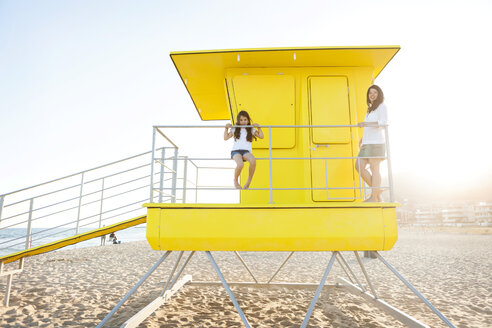 Mother and little daughter standing on a yellow lifeguard stand - VABF000698