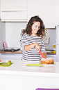 Woman cutting home-baked cake in the kitchen - SIPF000648