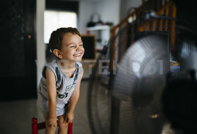 Grinning little boy standing in front of ventilator - JRFF000771