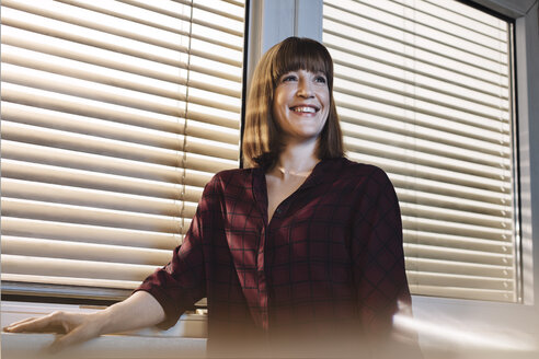 Portrait of smiling woman in front of window - GCF000207
