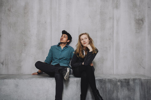 Young couple sitting in front of concrete wall - GCF000213
