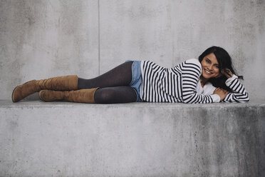 Female Indian laying on concrete wall - GCF000225