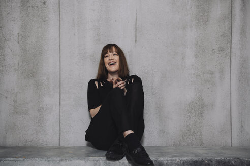 Woman sitting on concrete wall, laughing - GCF000231