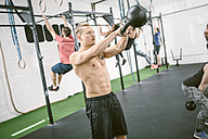People in gym training with kettle bells - MAD000989