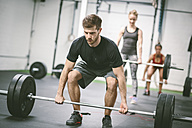 People in gym lifting weights - MAD000995