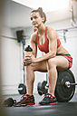Woman in gym taking a break, sitting on weights - MAD000998