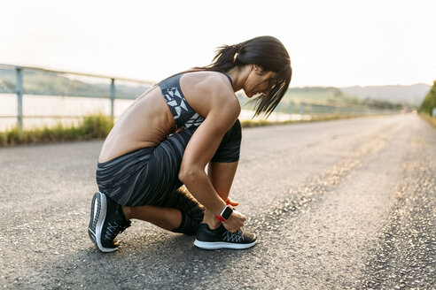 Woman tying laces of sports shoes - MGOF002052