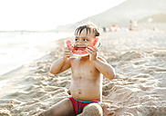 Little boy sitting on the beach at seafront eating watermelon - VABF000704