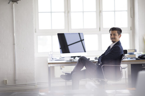 Businessman sitting in office, working on computer - FKF001905