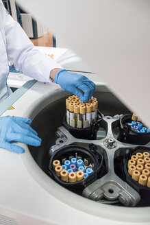 Laboratory technician in analytical laboratory taking test tubes out of centrifuge - ABZF000838