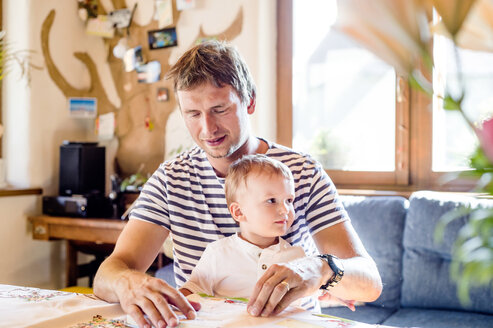 Father and son reading book at home - HAPF000617