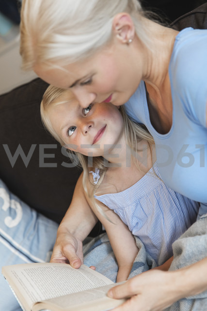 Mother and little daughter sitting together on couch with a book - MIDF000761