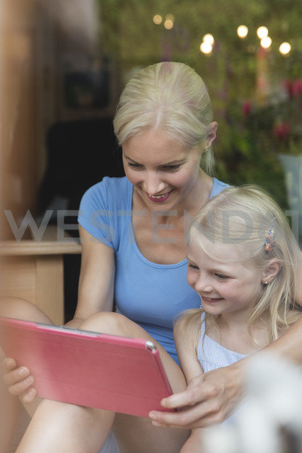 Mother and little daughter looking together at tablet - MIDF000764