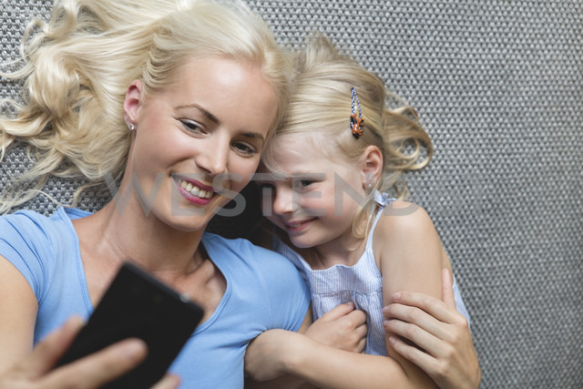 Mother and her little daughter lying on the floor taking selfie with smartphone - MIDF000767 - Miriam Dörr/Westend61