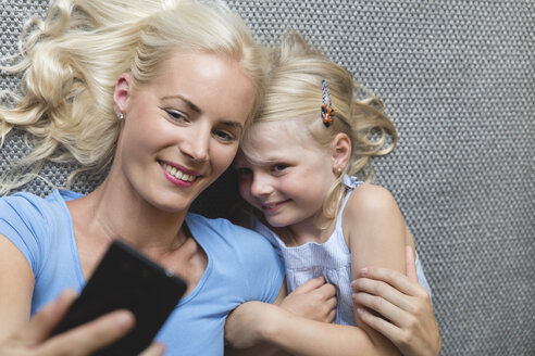 Mother and her little daughter lying on the floor taking selfie with smartphone - MIDF000767