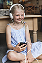 Portrait of happy little girl listening music with headphones and smartphone - MIDF000770
