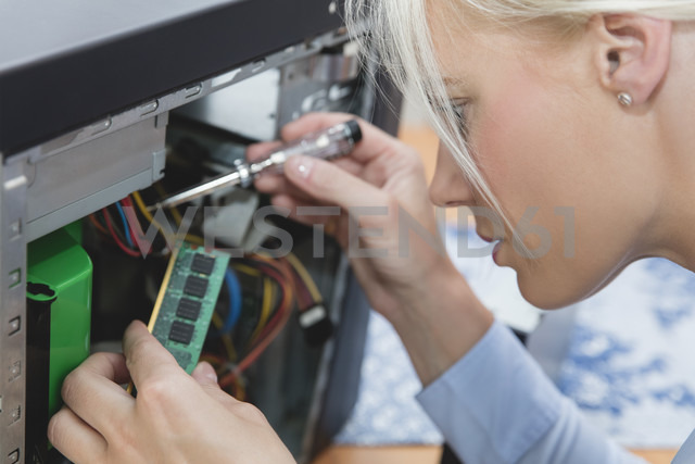 Woman assembling Random Access Memory at computer - MIDF000773 - Miriam Dörr/Westend61