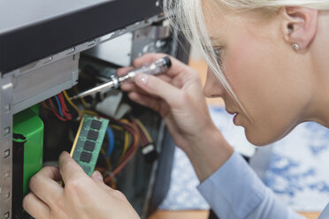 Woman assembling Random Access Memory at computer - MIDF000773