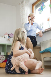 Businesswoman telephoning with smartphone while little daughter watching her - MIDF000776